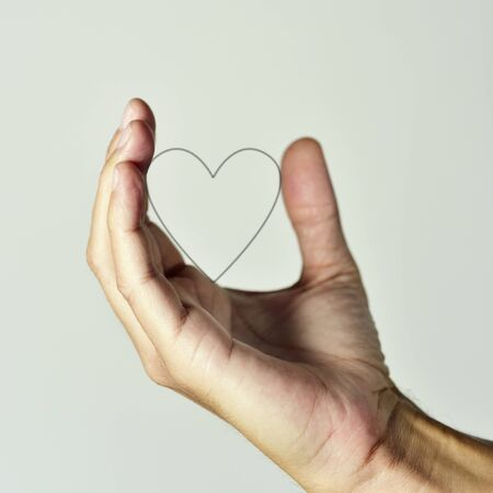 closeup of the hand of a young caucasian man holding the profile of a heart, against an off-white background Stock Photo