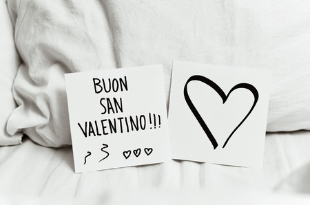 undone: closeup of a white paper note with the text buon san valentino, happy valentines day in italian written in it, and another paper note with a heart, on the white sheets of an undone bed