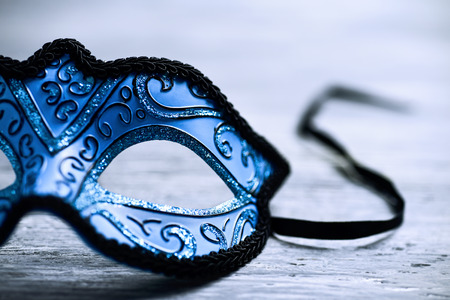 closeup of an elegant blue and black carnival mask on a rustic wooden surface Stock Photo