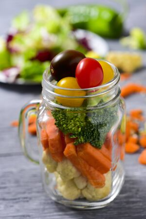 cornsalad: a salad with a mix of different vegetables, such as cauliflower, carrot, broccoli and cherry tomatoes of different colors served in a mason jar, on a gray rustic wooden table