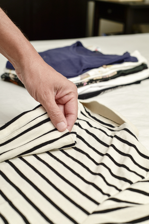 soltería: closeup of a young caucasian man folding a polo shirt, with a pile of folded clothes in the background