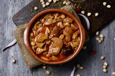 high-angle shot of an earthenware bowl with spanish callos, a typical beef tripe stew with chickpeas, morcilla and chorizo, on a rustic wooden table