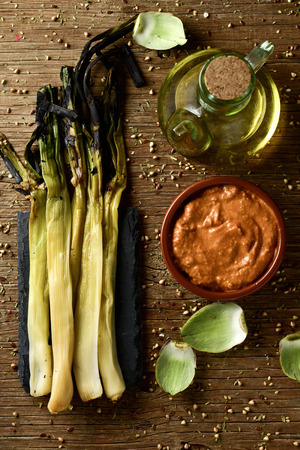 calsotada: high-angle shot of some roasted calcots, sweet onions typical of Catalonia, Spain, and an earthenware bowl with romesco sauce to dip them in it, and a cruet with olive oil on a rustic wooden table
