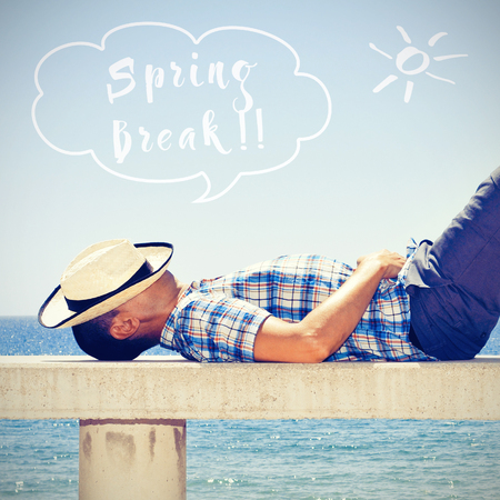 a young caucasian man with a straw hat on his face lying down in a street bench near the sea and text spring break in a speech balloon