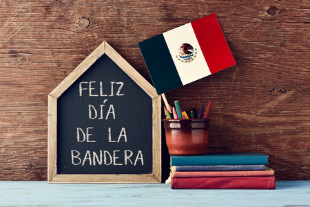 old flag: a house-shaped chalkboard with the text Feliz Dia de la Bandera, Happy Flag Day written in Spanish, the flag of Mexico in a pot with some pencil crayons and a pile of old books on a wooden surface Stock Photo