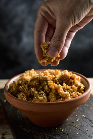 closeup of a young man eating couscous with his fingers from an earthenware casserole placed on a rustic wooden table Stok Fotoğraf