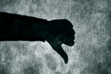 appalling: the shadow of a man giving a thumbs-down sign behind a gray fabric