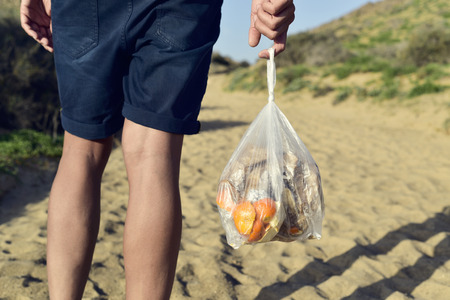 closeup of a young caucasian man seen from behind carrying a transparent plastic bag with leftovers as he walks by a sandy track Stockfoto