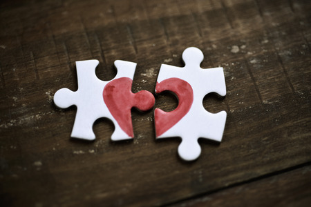 rupture: closeup of two separated pieces of a puzzle which together form a heart on a rustic wooden surface, depicting the idea of rupture or cooperation Stock Photo
