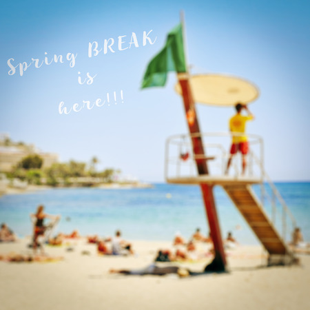 vac: text spring break is here on a blurred picture of a beach full of unrecognizable people sunbathing