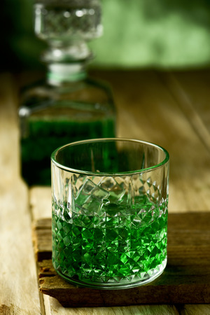 closeup of a glass with dyed green whiskey on a wooden rustic surface and a liquor bottle with dyed green in the background Stock Photo