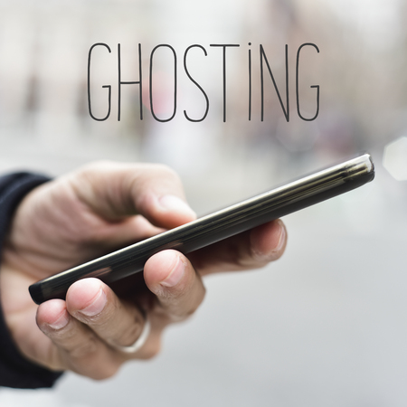 ceasing: closeup of a young caucasian man using a smartphone in the street and the word ghosting Stock Photo