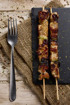 high-angle shot of some barbecued spiced chicken meat skewers on a slate tray, placed on a rustic wooden table Foto de archivo