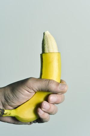 close-up van de hand van een jonge man met een banaan waarvan het topje van de huid is verwijderd, met afbeelding van een besneden mannelijk lid