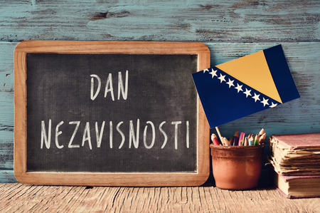 bosna: a chalkboard with the text Dan Nezavisnosti, Independence Day written in Bosnian, a pot with pencils, some books and the flag of Bosnia and Herzegovina, on a wooden desk Stock Photo