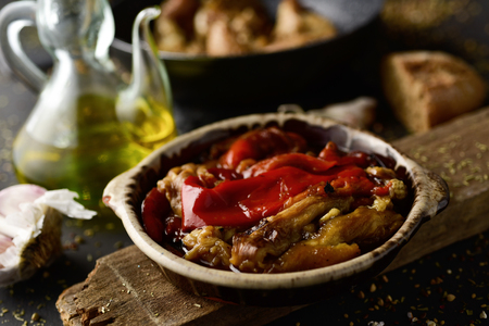 a plate with escalivada, a typical dish of Catalonia, Spain, made with grilled and peeled eggplant, red pepper and onion, on a rustic wooden table next to a cruet with olive oil Stock Photo