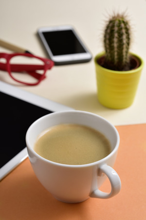 closeup of an office desk full of things, such as a cup with white coffee, a pen, a tablet, a smartphone, a cactus and a pair of red eyeglasses Stock Photo