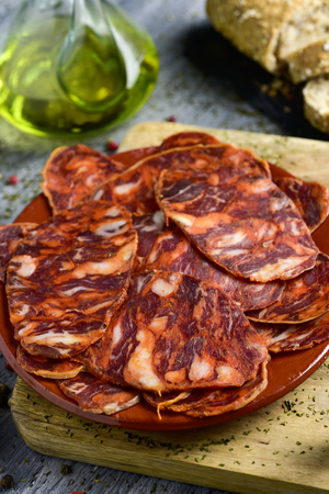 closeup of an earthenware plate with some slices of spanish chorizo, a cured pork sausage, on a rustic wooden table, and some slices of bread and a cruet with olive oil in the background
