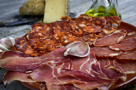 a plate with an assortment of different spanish cold meats as chorizo, cured pork tenderloin and serrano ham, and a piece of manchego cheese, bread and a cruet with olive oil in the background