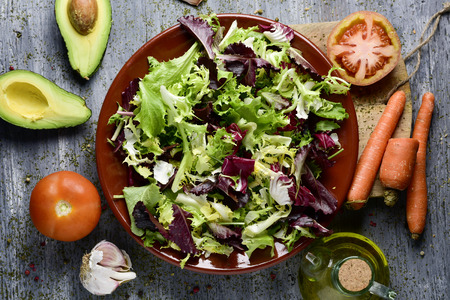 escarola: high-angle shot of a rustic wooden table with some ingredients to prepare a salad; a plate with lettuce mix, tomatoes, an avocado cut in half, some carrots and a cruet with olive oil Foto de archivo