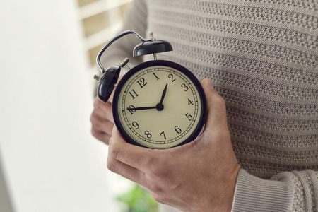 closeup of young Caucasian man winding or adjusting the time of an alarm clock Stock Photo - 73151427