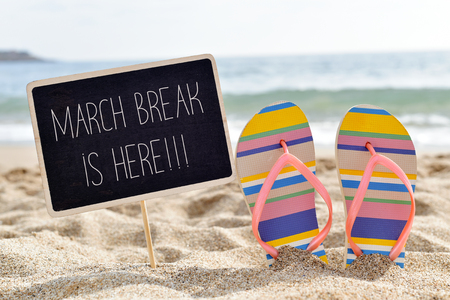 closeup of a chalkboard with the text march break is here written in it and a pair of flip-flops on the sand of a lonely beach