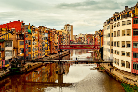 ferro: a view of the Onyar River as it passes through Girona, in Spain, some of its characteristics colorful houses and bridges, highlighting the red one built by Eiffel, and the Old Town on the left Stock Photo