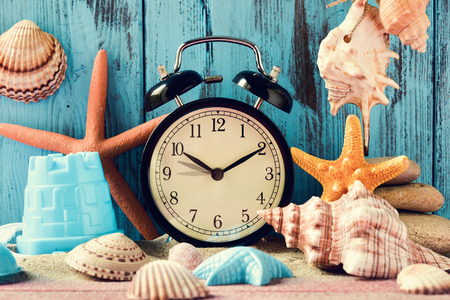 adjusted: an alarm clock being adjusted forward one hour at the beginning of the summer time, many conches and starfishes, and a beach pail, on a pile of sand, against a bright blue rustic wooden background