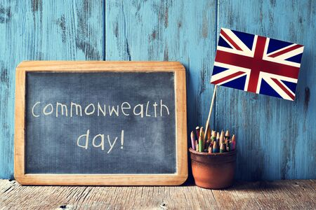 a wooden-framed chalkboard with the text commonwealth day written in it and the Union Flag in a pot of pencils, against a blue rustic wooden background Stock Photo