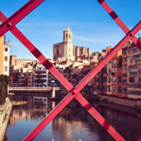 ferro: a view of Girona, in Spain, the Onyar River and the Old Town of the city, highlighting the Cathedral on the right, seen through the structure of the characteristic red bridge built by Eiffel Stock Photo