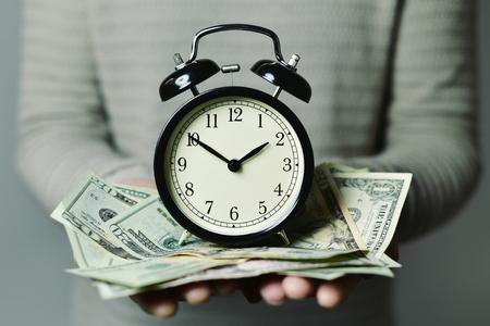 Nahaufnahme eines jungen kaukasischen Mannes mit einem Wecker und viele US-Dollar-Banknoten in seinen Händen, Darstellung der Idee, dass Zeit Geld ist