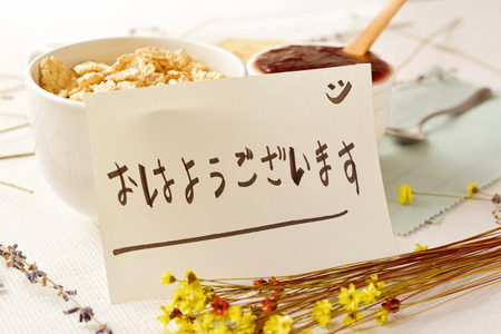 closeup of a table set for breakfast with a porcelain bowl with cereals, some toasts a bowl with jam and a note with the text good morning written in japanese