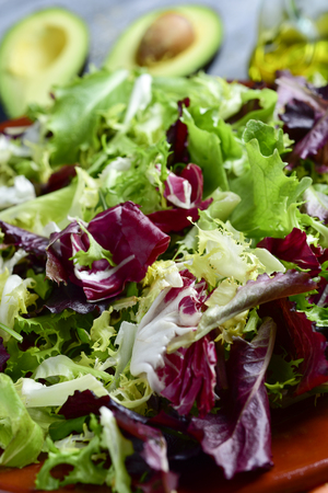 closeup of a plate with a green salad, with lettuce mix and an avocado cut in half and a cruet with olive oil in the background Stock Photo