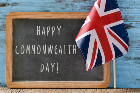 a wooden-framed chalkboard with the text happy commonwealth day written in it and the Union Flag against a blue rustic wooden background