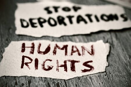 displaced: closeup of some pieces of paper with the text human rights and stop deportations handwritten in them on a rustic wooden surface