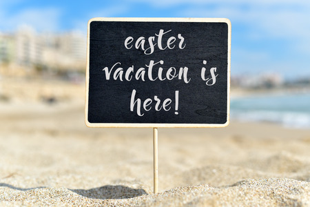 a bathing place: closeup of a black signboard with the text easter vacation is here written in it, on the sand of a beach Stock Photo