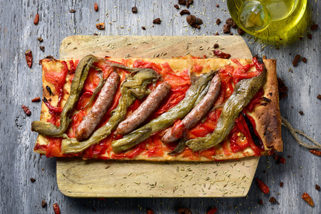 llonganissa: high-angle shot of a slice of coca de recapte, a typical catalan savory cake similar to pizza, made with grilled eggplant and red pepper, and pork sausage, on a rustic wooden table Stock Photo