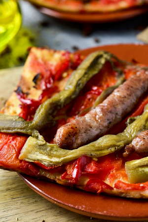 llonganissa: closeup of a slice of coca de recapte, a typical catalan savory cake similar to pizza, made with grilled eggplant and red pepper, and pork sausage, on a rustic wooden table