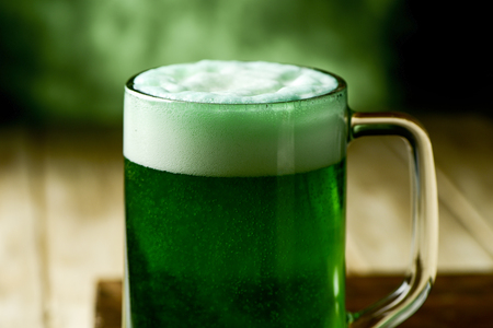 jarra de cerveza: closeup of a glass jar with dyed green beer on a wooden rustic surface