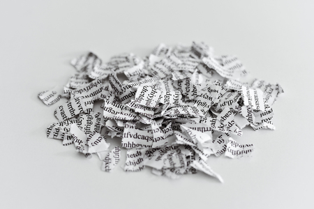 a printed letter or document broken into a thousand pieces Standard-Bild