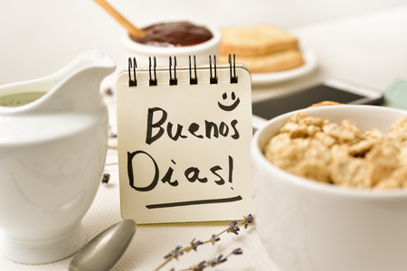 closeup of a table set for breakfast with a porcelain bowl with cereals, some toasts a bowl with jam and a note with the text good morning written in it