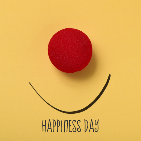 nariz roja: the text happiness day, a red clown nose and a smile drawn on a yellow background