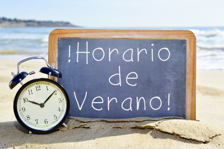 an alarm clock and a chalkboard with the text horario de verano, summer time in spanish, on the sand of a beach