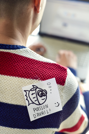 closeup of a young caucasian man seen from behind using a laptop, with a note with a fish and the text poisson d avril, a french holiday similar to april fools day, attached with tape to his back
