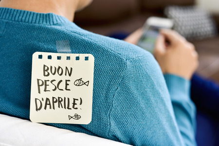 closeup of a young caucasian man seen from behind using his smartphone, with a note with the text buon pesce d aprile, happy april fools day in italian, attached with tape to his back Stock Photo