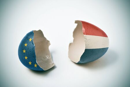 populist: the two halves of a cracked eggshell, one patterned with the flag of the European Community and the other one patterned with the flag of the Netherlands