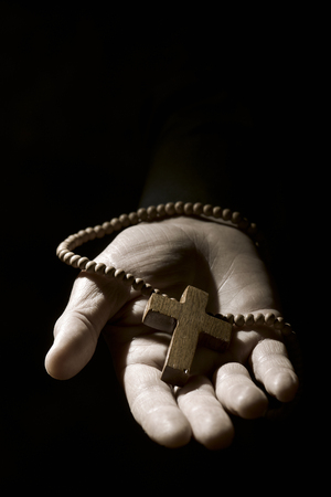 spiritualism: closeup of the hand of a young caucasian man with a rosary with a wooden cross in it