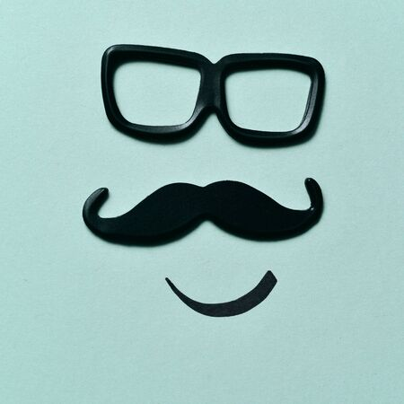 paternal: a pair of black plastic-rimmed eyeglasses and a mustache depicting a man face, on a blue background Stock Photo