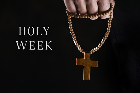 closeup of the hand of a young caucasian man praying with a rosary with a wooden cross in it, and the text holy week against a black background