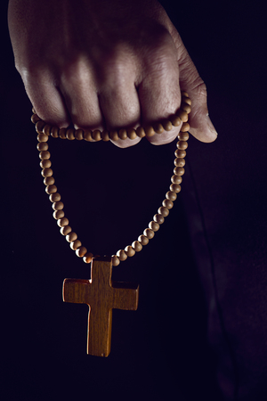 closeup of the hand of a young caucasian man praying with a rosary with a wooden cross in it Stock Photo